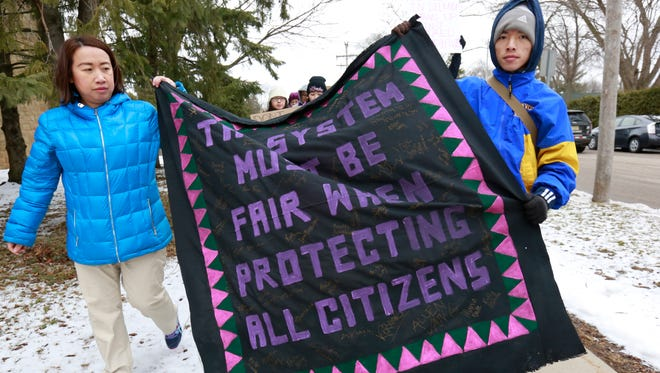 "Participants march with a Hmong quilt during a youth-led rally ""A Hate Crime Is A Crime"" Saturday, March 18, 2017, at the Goerke Field in Stevens Point, Wisconsin."