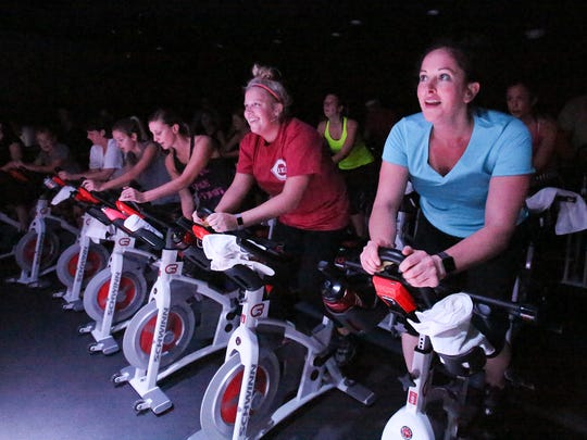 Julie Purcell, right, and her sister-in-law Jessica Purcell exercise in an indoor cycling class at the Cyclebar in St. Matthews. The class uses low light and music to enhance the experience.