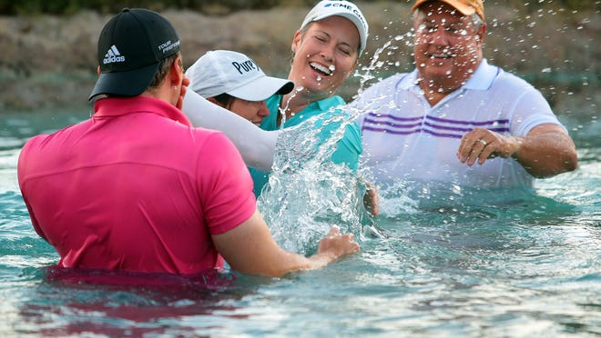 Brittany Lincicome and caddie Missy Pederson embrace in Poppie's Pond after jumping in with Lincicome's father Tom Lincicome (right), and fiancé Dewald Gouws (left), following her victory at the ANA Inspiration on Sunday at Mission Hills Country Club in Rancho Mirage, Calif. Lincicome won after three playoff holes with Stacy Lewis. Lincicome won the tournament in 2009 and becomes the eighth person to win it multiple times.