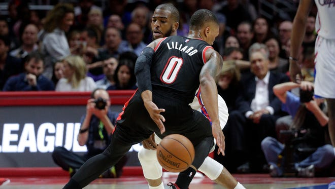 Portland Trail Blazers' Damian Lillard, front, tries to get the ball past Los Angeles Clippers' Chris Paul during the first half of an NBA basketball game Wednesday, March 4, 2015, in Los Angeles.