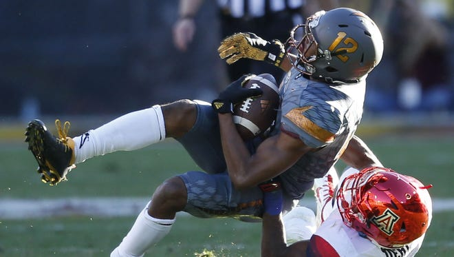 Arizona State wide receiver Tim White is tackled by Arizona DaVonte Neal, #19, during the Territorial Cup game at Sun Devil Stadium in Tempe on November 21, 2015.