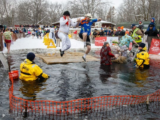 Partipants jump into icy water to benefit the Special Olympics during the Muskego Polar Plunge at Muskego County Park on Feb. 11, 2018.