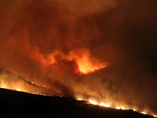 In this June 30, 2016, photo, a wildfire fire burns