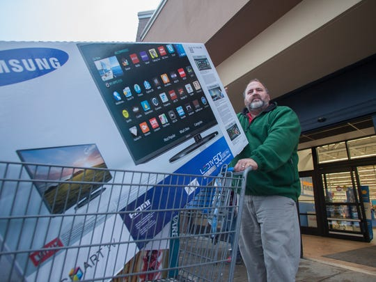"Tom Cummings of Jericho, a Burlington School teacher, leaves the Williston Walmart on Black Friday with a 50"" TV."
