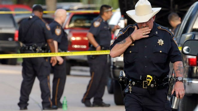 Harris County Sheriff's Department Sgt. D.J. Hilborn, right, walks away from the scene of a multiple shooting Sunday, Aug. 9, 2015, in Houston. Eight people, including five children and three adults, were found dead late Saturday inside a Houston-area home following the arrest of a man who exchanged gunfire with police, Texas authorities said Sunday. (AP Photo/David J. Phillip)