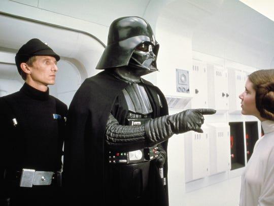 Darth Vader, center, makes a point to Princess Leia,