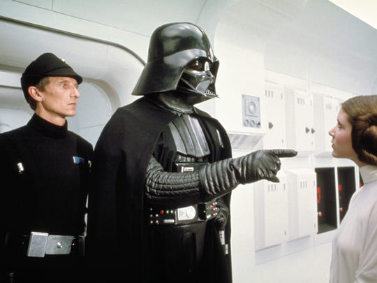 """Darth Vader, center, makes a point to Princess Leia, played by actress Carrie Fisher, in the original """"Star Wars"""" film, which was released in 1977. Actor James Earl Jones of Pawling provided the voice for Darth Vader."""