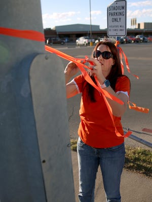 Melissa Stapp ties orange ribbons to posts around San Angelo Stadium to decorate for Central's game against Allen on Friday.
