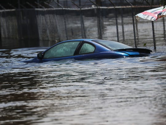The roof of a submerged car peeks over flood waters