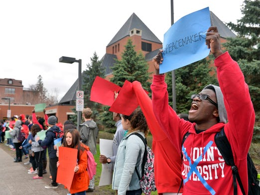 St. John's University junior Emmanuel Gbutu Freeman, a junior from Liberia, and about 125 other students protest Friday outside Sexton Commons, calling for cultural sensitivity, unity and other social justice themes as well as changes to the way the schools handle discrimination complaints.