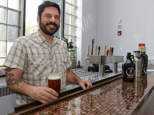 Owner Joe Fisher behind the counter at Man Skirt Brewing on Main Street in Hackettstown.