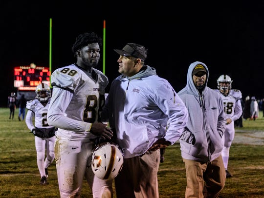 Former Central Head Coach Andy Owen (center) talks to Rayzel Joiner (88) as they walk to the locker room after the regional championship game in St. Leon, Ind., Friday, Nov. 10, 2017.