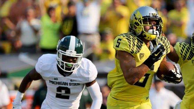 With Michigan State's Darian Hicks, left, in pursuit, Oregon's Devon Allen runs to the end zone Sept. 6, 2014.