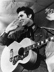 Elvis Presley is shown with his Gibson J-200 guitar in a 1957 MGM studio publicity photo.
