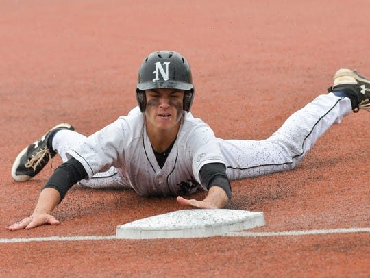 Northville's Trevor Schornack goes head first with the slide into third base in a 5-3 regional semifinal win over Farmington.