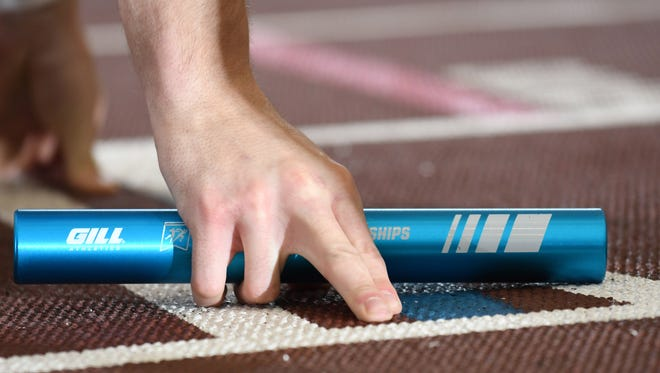 A runner holds a baton in the starting blocks.