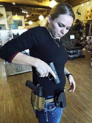 Alexandra Wilson, marketing director and firearms instructor at Sportsman's Elite indoor shooting range and pro shop at 4520 Doniphan, shows two varieties of handgun holsters.