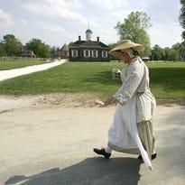 A worker dressed in colonial-era walks through colonial Williamsburg, Virginia.