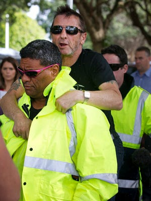 Phil Rudd, center, drummer for the rock band AC/DC, jumps onto the back of his security guard after his short court hearing in the High Court at Tauranga, New Zealand, Wednesday, Nov. 26, 2014.