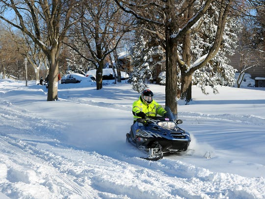 Joe Frydel's snowmobile is perfect for transportation as his neighbors dig out in northwest Lansing on Monday after the area's heavy snowstorms.
