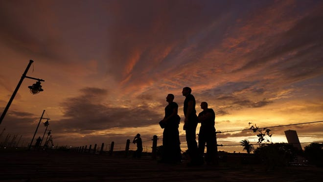 Port Arthur firefighters stare at a sea wall at sunset as they wait for Hurricane Laura to make landfall, Wednesday, Aug. 26, 2020, in Port Arthur, Texas.