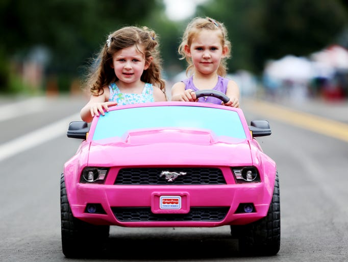 "Sophia Glinsman, 3, and Daynarae Dietrich, 4, right, drive together in a powered Mustang car during the Open Streets Sunday, July 20, 2014. City's first Open Streets event, aiming to build community, promote active transportation and increase awareness of streets as ""public facilities with multiple use,"" according to the city's website. Laurel Street, from Remington and Lessar Drive, and Whedbee Street, from Laurel Street to Prospect Road, the city closed for the event."