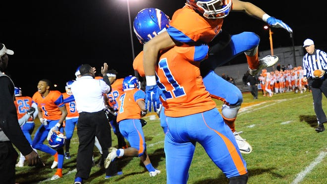 Millville's Ahmad Corley lifts up Marcial Ramos as they celebrate after defeating Cherokee 22-14 in a group 5 first round playoff game on Friday. 11.11.16 Joe Warner/For the Courier-Post