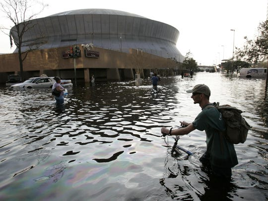 Eric Gay/AP file A man pushes his bicycle through floodwaters