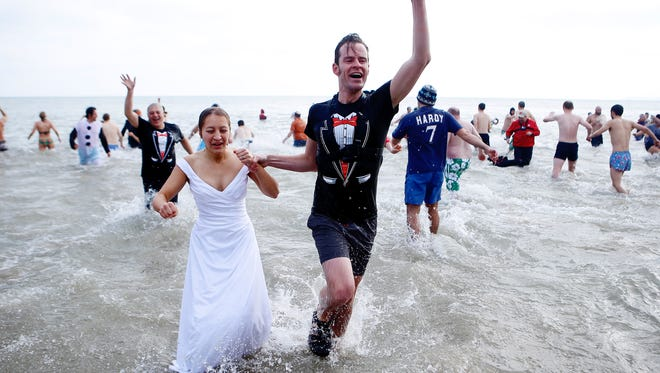 A couple dressed up as a wedding couple emerge from frigid Lake Michigan during the annual Milwaukee Polar Plunge at Bradford Beach in Milwaukee on Jan 1, 2016.