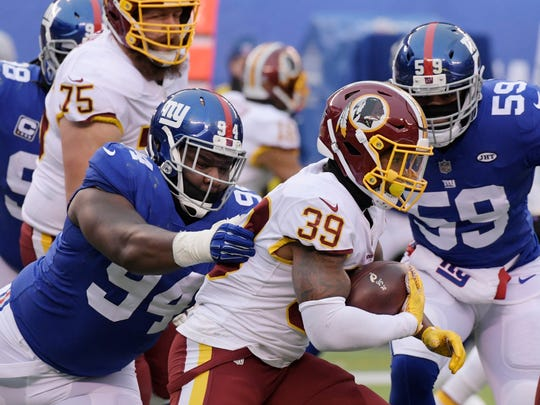 New York Giants' Dalvin Tomlinson (94) tackles Washington Redskins' Keith Marshall (39) during the second half of an NFL football game Sunday, Dec. 31, 2017, in East Rutherford, N.J. (AP Photo/Bill Kostroun)
