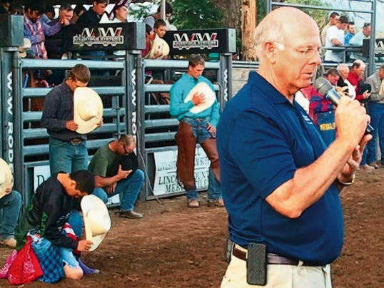 The cowboys kneel and bow their heads as Steve Pearce says a prayer before the beginning of last year's 4th of July rodeo in Capitan.