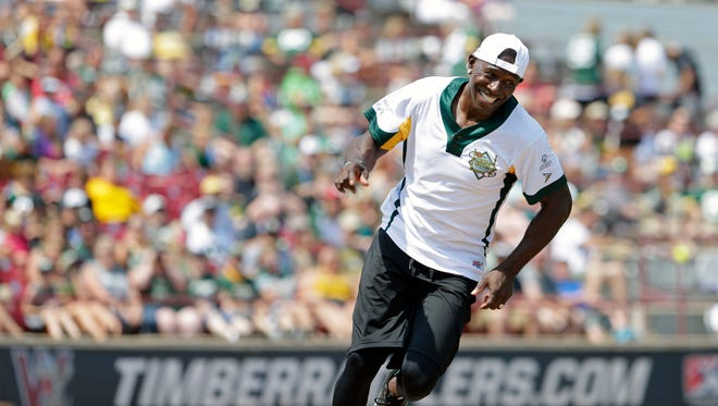Donald Driver smiles after hitting a home run as he joins friends for a charity softball game Sunday at Neuroscience Group Field at Fox Cities Stadium in Grand Chute.