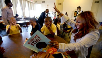 """Gina Neely, right, reads """" Chocolate Me!"""" to second grade students, from left, Jaylyn Ezell, Tristian Johnson, and Tyrone Scott during Greater Memphis Media's I Love Reading initiative at Little Flower Primary School."""