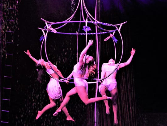 Aerialists dazzle and shimmer on a chandelier high