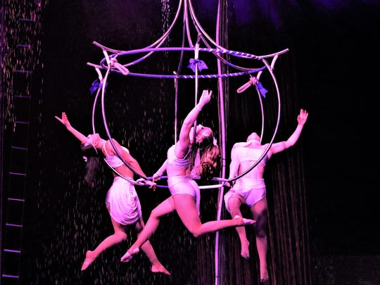 Aerialists dazzle and shimmer on a chandelier high above the ground in a Cirque Italia performance.