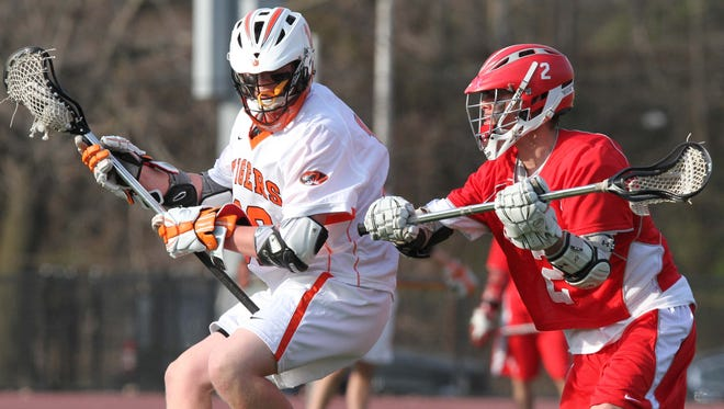 White Plains' Kevin Trapp sets up for a goal under pressure from North Rockland's Joe Tisbie in a boys lacrosse match at White Plains High School April 8, 2013. White Plains defeated North Rockland 6-5. (Matthew Brown/The Journal News)