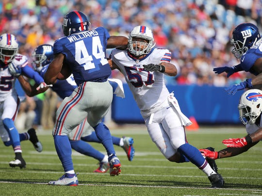 Bills linebacker Lorenzo Alexander (57) trying to wrap up Giants runner Andre Williams (44).