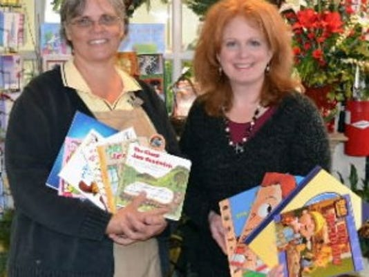 Deb Chrisley, store manager at Royer's West York store, left; and Deb Sullivan, community relations director, York County Libraries, are shown with books collected at Royer's West York and East York stores during the 2011 Bouquet for Books drive. (Submitted photo)