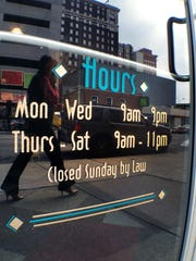 "A sign on a liquor store reads ""Closed Sunday by Law."""
