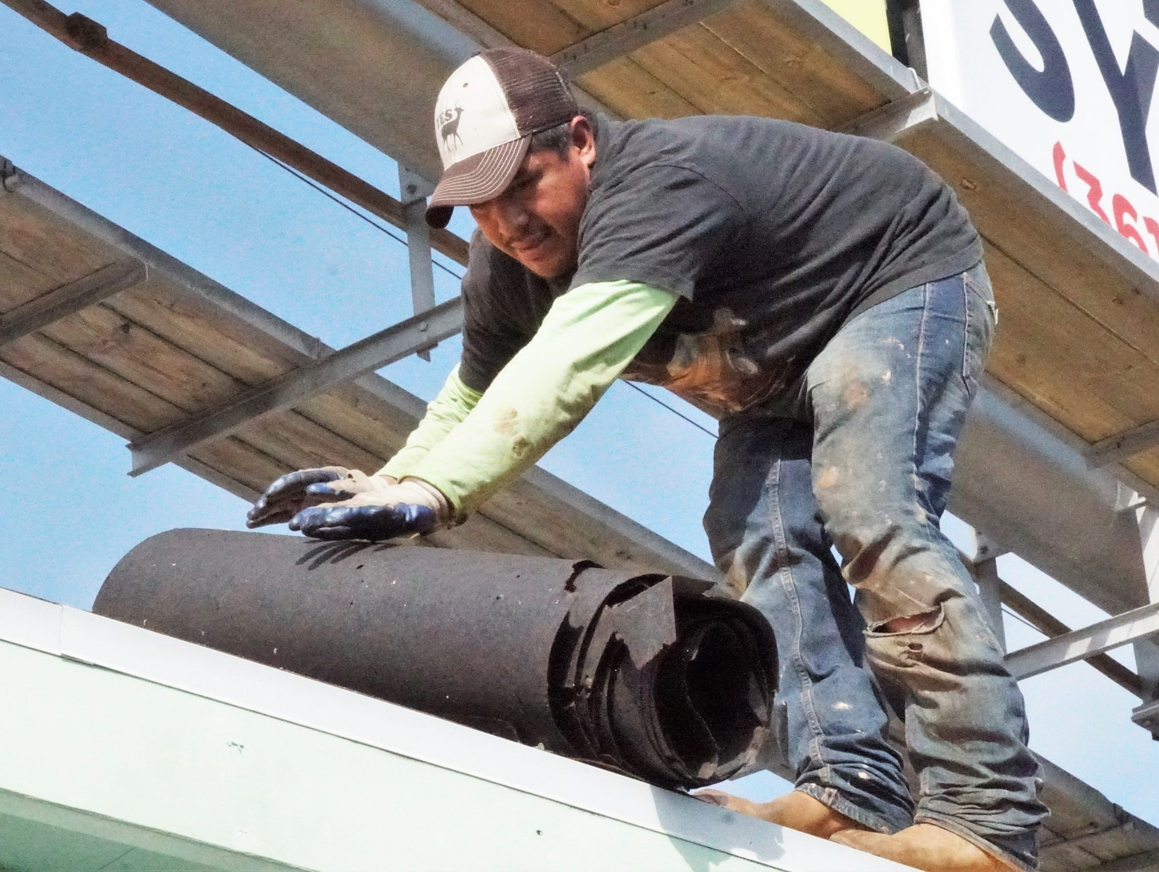 A worker rolls up tattered roofing material that is