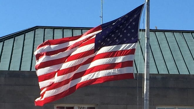 A cold north wind gives the American flag at the U.S. Courthouse in downtown Asheville a good workout at midday Friday.