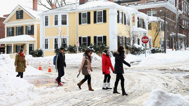 Pedestrians navigate snow-covered streets on Feb. 10, 2015 in Cambridge, Mass.