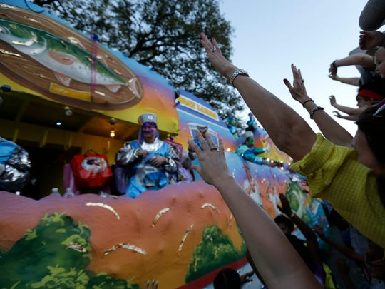 Parade-goers try to catch beads and trinkets being thrown from floats the Krewe of Bacchus Mardi Gras parade rolls down Napoleon Ave. in New Orleans, onMarch 2, 2014.