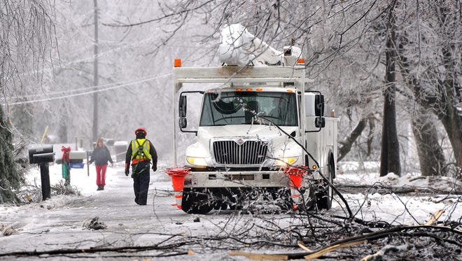 A utility truck is parked on a street to help restore power to a neighborhood in North Lansing, Mich., on Dec. 22, 2013.