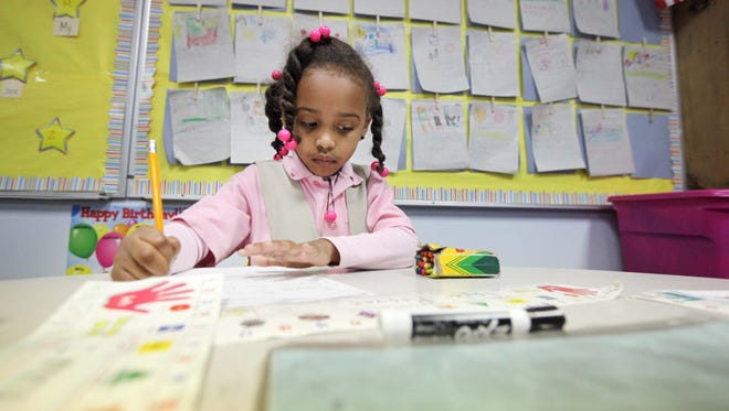 Taylor Reaves, 5, a kindergartner at the Reach Academy for Girls, works Tuesday on a numbers-recognition assignment.