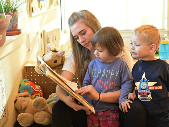 Moriah Kunau reads to Avonelle Hays and Jaxon Wolff