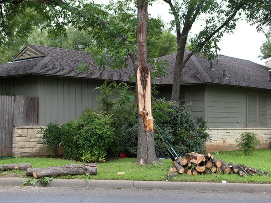 Chopped wood from a broken tree are lined up next to the curb after was damaged during a severe thunderstorm from Friday night. Residents throughout San Angelo worked to clear debris Saturday, June 24, 2017.
