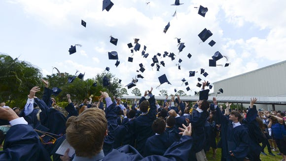 Holy Trinity seniors toss their caps in the air after receiving their diplomas Saturday.