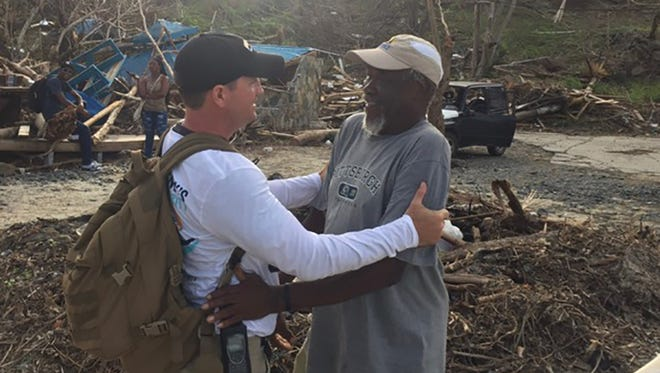 """John McInnis, owner of the Flora-Bama and president of the Kenny Chesney Love for Love City Foundation, greets """"Foxy"""" on Jost Van Dyke, an island in the British Virgin Islands. The Foundation has been making weekly supply trips to the Virgin Islands to help with relief efforts after Hurricane Irma slammed into the area in September."""