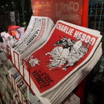 "An early morning commuter walks past a newsstand displaying the new edition of the French satirical paper ""Charlie Hebdo"" at Gare du Nord train station in Paris on Feb. 25, 2015."